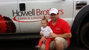 Carl Howell of Howell Brothers Lawn and Landscaping with little helper